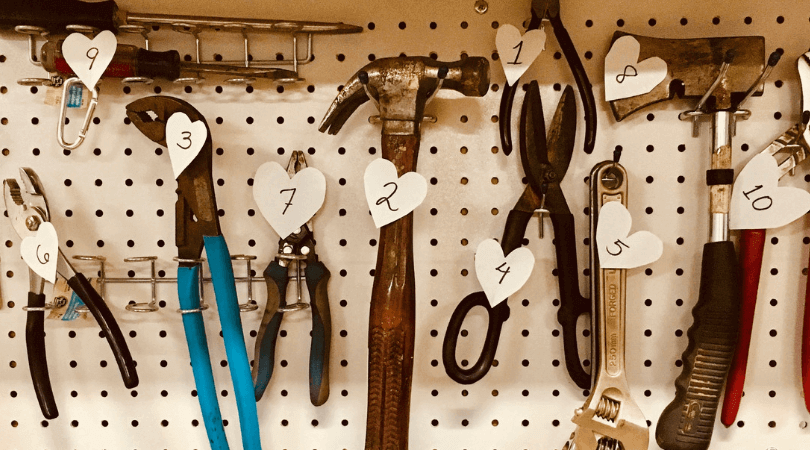 tools on pegboard labeled with numbered hearts