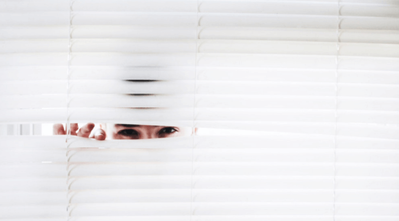 man peering through window blinds