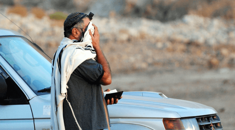 jewish man praying in tefillin and a tallit with siddur with face covered