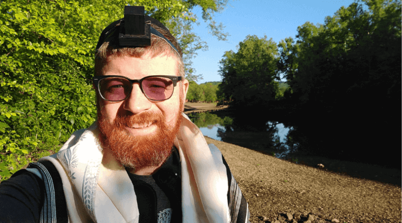 ken lane wearing tefillin beside a riverbank