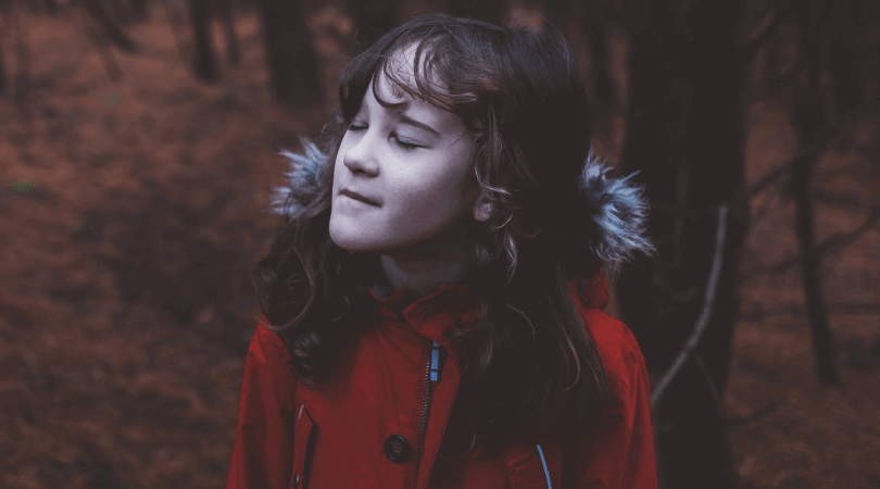 meditating child with eyes closed and red coat in the woods