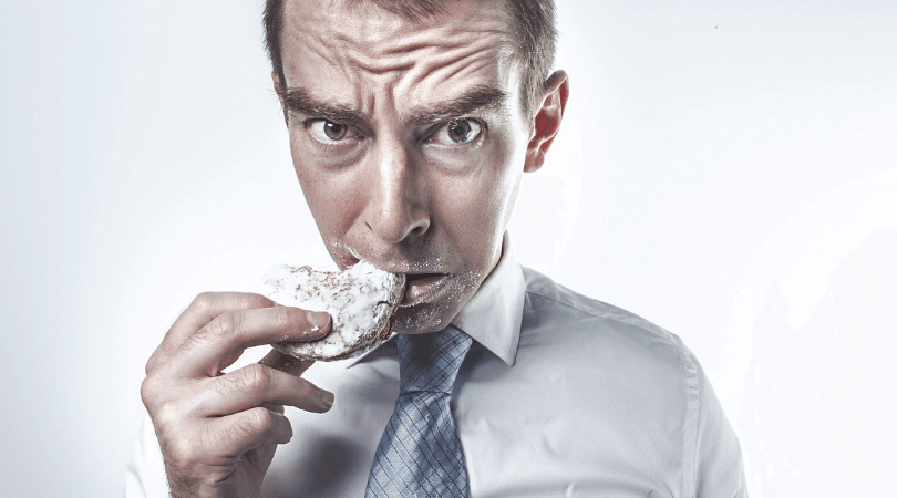 man regretably eating a cookie